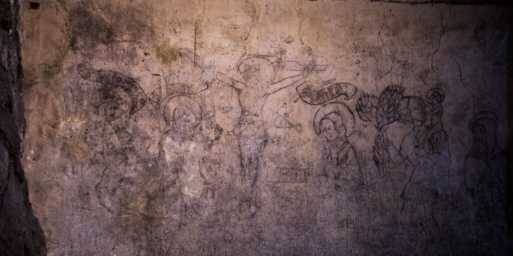Some prisoners were able to draw on the dungeon walls. This drawing, made by prisoners, is thought to contain an image of Christ on the cross and other religious figures.