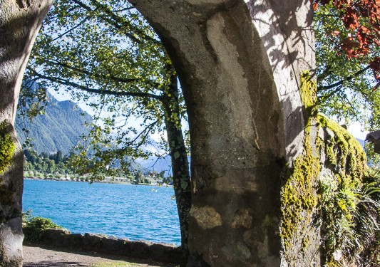A view of Lake Geneva through a garden arch by Castle Chillon