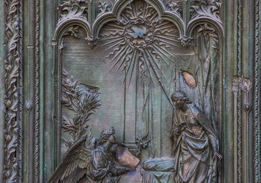 Detail of the carving on the door of the cathedral in Milan. In this picture, an angel has come with a message or gift to the person (Zachariah?) standing on the right. You can see God's presence in the form of the dove at the top.