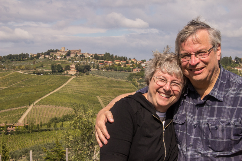 Dave and Karen pose in front of a view of a distant hill town in Tuscany.